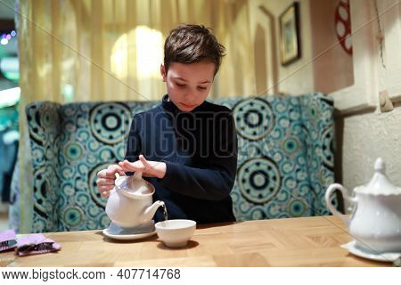 Boy Pouring Tea In Restaurant