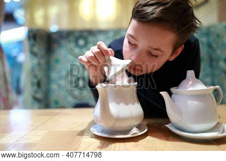 Child Checks Brewing Of Tea