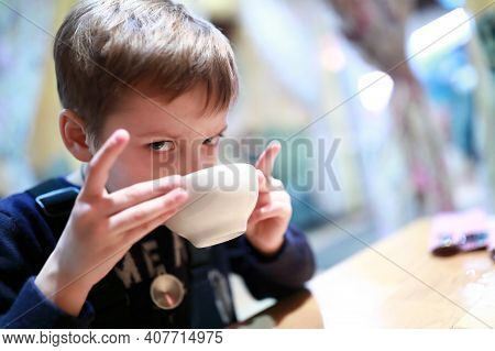 Kid Drinking Tea In Restaurant