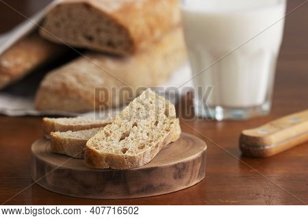 Baguette And Baguette Slices On A Wooden Table.