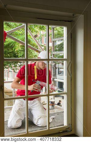 Zwolle Netherlands Jul 02 2020 Painter Applying Chaulk Sealant. Silicone Window Seal And Waterproofi