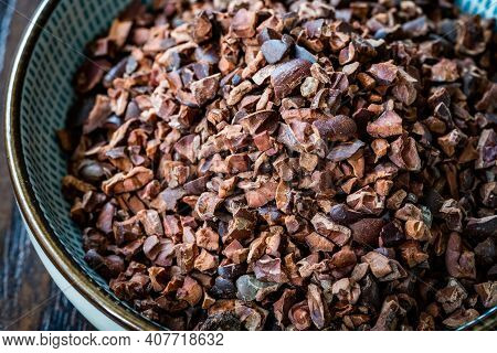 Chocolate Cacao Nibs Or Cocoa Nibs In Bowl Ready To Use On Dark Wooden Surface.