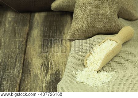 Coconut Flakes In A Wooden Spoon On A Wooden Background. Coconut Flakes On A Wooden Ladle With Space