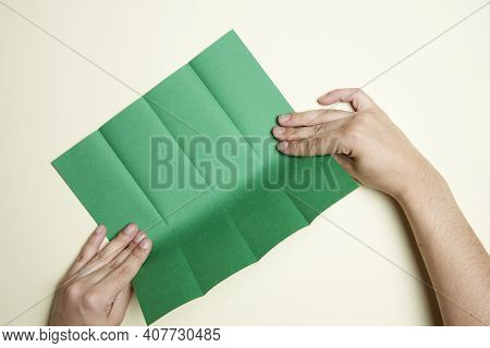 Young Hands Marking Folds On A Square Of Green Paper To Make An Origami Figure. Concepts: Origami, H