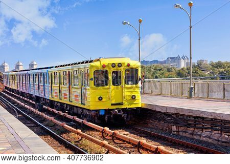 A Bright Yellow Metro Train Departs From The Platform And Rushes Along The Metro Bridge In Kyiv To T