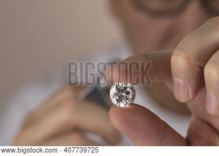 Jeweller Asian Man Looking At Diamond Through Magnifying Glass. Diamond Dealer Evaluating And Gradin