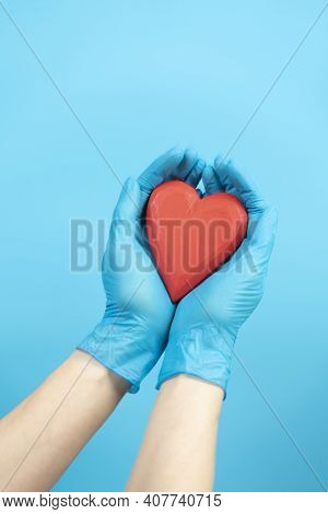 Female Hands Wearing Blue Medical Gloves Holding Red Heart Over Light Blue Background. Health Care,