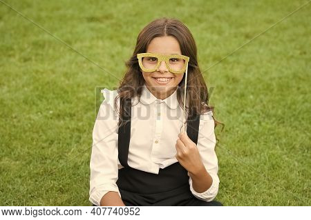 School Party. Happy Child Hold Prop Glasses. Party Girl On Green Grass. Small Pupil With Party Look.