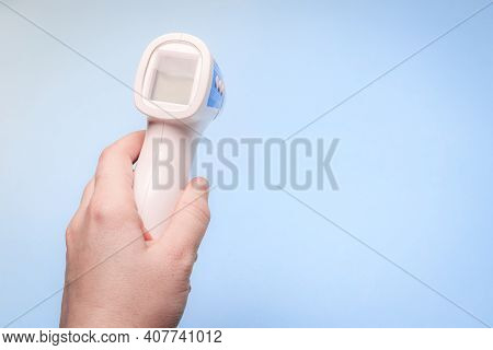 Infrared Thermometer On A Blue Background In Your Hand. The Thermometer In His Hand . Prevention. No