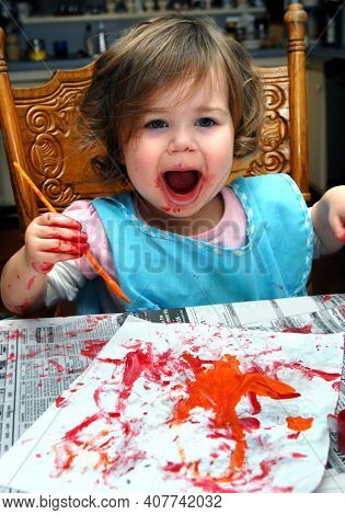 Toddler Squaels With Joy As She Admires Her Creation.  She Is Painting With A Brush Onto A White She