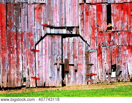 Background Image Of Barn Front.  Building Is Red, Wooden, Fading And Weathered.  Image Shows Broken