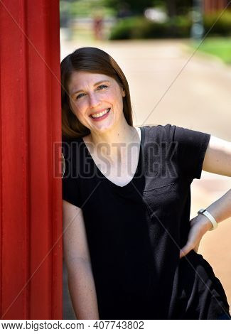 Young Woman Leans Against A Red Telephone Booth In Downtown Collierville, Tennessee.  She Has On A B