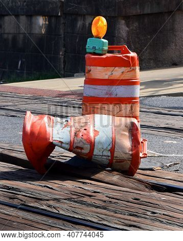 Two Construction Barrels Sit On Railroad Tracks In Downtown Memphis, Tennessee.  One Barrel Has Been