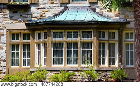 Long Bay Window On Stone House Seven Windows And Is Trimmed In Off-white And Tan.  Home Is Stone And