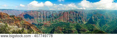 Waimea Canyon Panorama On A Beautiful Partly Cloudy Day. Perfect Orange And Green Lush Landscape Vie