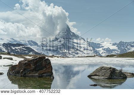 Rocks In Lake Stillisee And Clouds Building Up Over The Matterhorn From Zermatt