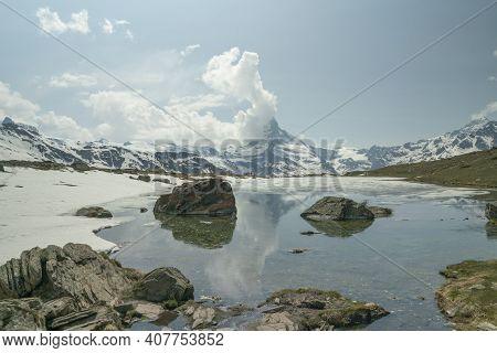 Shot Of Lake Stillisee And Clouds Building Up Over The Matterhorn From Zermatt