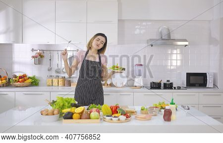 Happy Young Asian Woman Dancing And Singing While Holding Bowl With Salad Near Table And Fresh Salad