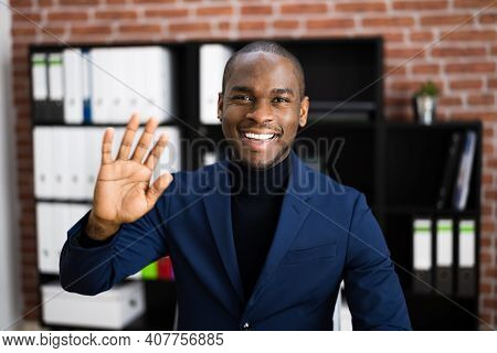 African American Elearning Videoconference In Office Waving Hand