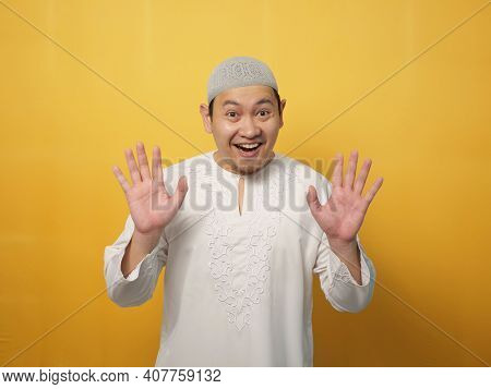 Portrait Of Muslim Man Wearing Hijab Looking At Camera Smiling And Waving His Hands Saying Hi Or Goo