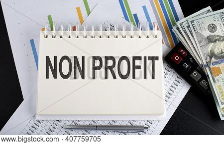 Non Profit Text Written On The Notebook With Chart,calculator And Dollars