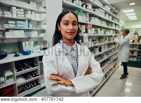 Young Female Pharmacist With Crossed Hands And Labcoat In Chemist With Colleague Working In Backgrou