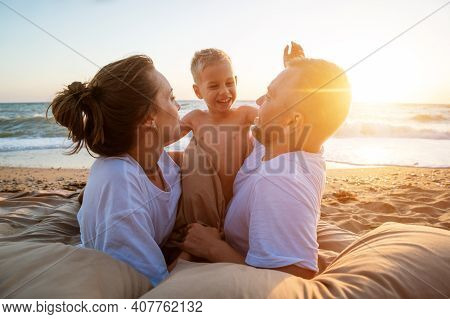 Young Happy Family On The Beach At Sunset Lie On A Blanket, The Concept Of Family Vacations In Natur