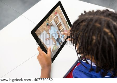 Mixed race schoolboy using digital tablet on video call with male teacher. Online education staying at home in self isolation during quarantine lockdown.