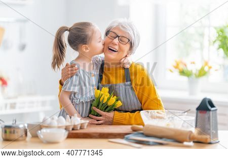 Happy loving family are preparing bakery together. Little girl is giving flowers to her granny in the kitchen.