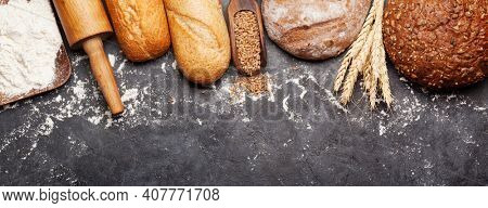 Various bread with wheat, flour and utensils on stone table. Homemade cooking concept. Top view flat lay