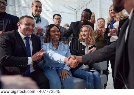 employees shaking hands at a corporate meeting.