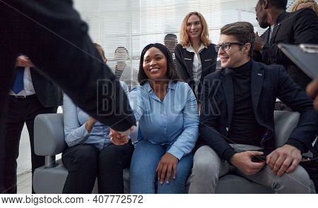 employees congratulating their colleague at a work meeting.
