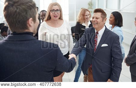 business people shaking hands in a crowded office.