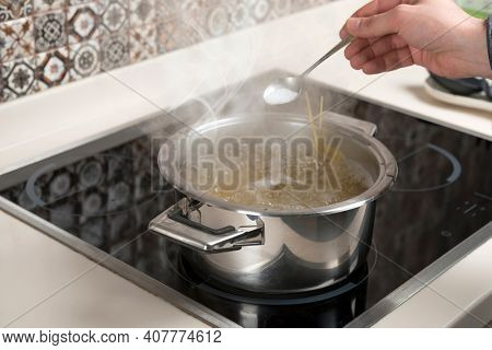 Male hand adding spoon of salt in cooking pan
