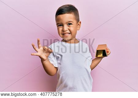 Adorable latin toddler holding gold ingot doing ok sign with fingers, smiling friendly gesturing excellent symbol