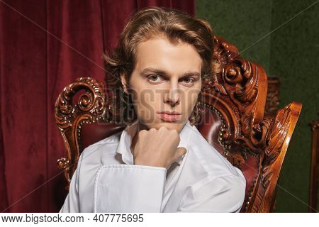 Men's beauty, fashion. Portrait of a handsome young man with wavy blond hair wearing elegant white shirt sitting in luxury apartments.