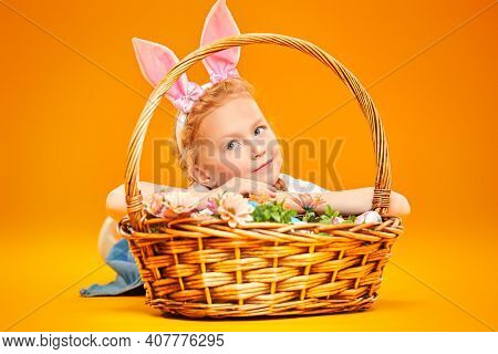 Cute redhead girl with bunny ears lies with a basket full of flowers and painted Easter eggs on a yellow background. Happy childhood. Easter holiday.
