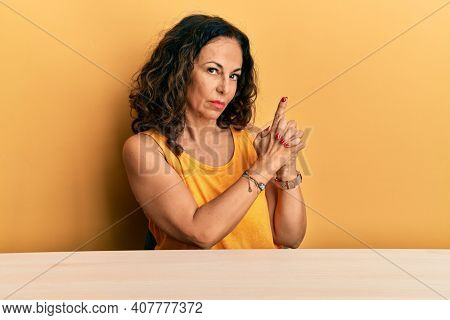 Beautiful middle age woman wearing casual clothes sitting on the table holding symbolic gun with hand gesture, playing killing shooting weapons, angry face
