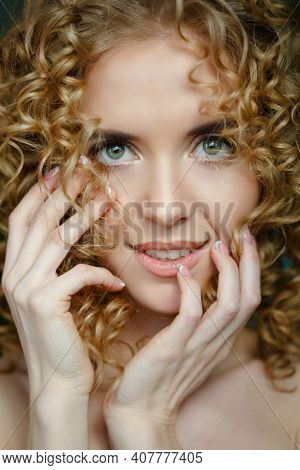 Beautiful blonde with afro curls. A stunning beauty with a voluminous hairstyle, updo. Perfect skin, beautiful makeup and stylish manicure.