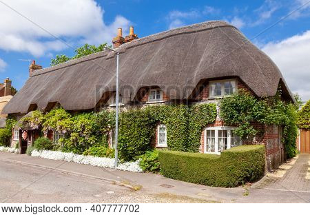 Street view of traditional english country thatched cottage decorated with plants and blooming flowers in rural Southern England UK