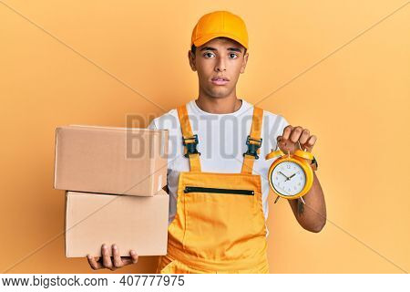 Young handsome african american man holding delivery box and alarm clock for express service relaxed with serious expression on face. simple and natural looking at the camera.