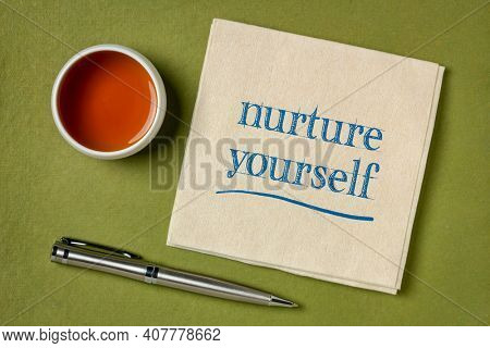 nurture yourself - inspirational handwriting on a napkin with a cup of tea, self care concept