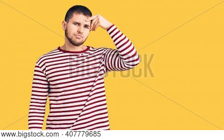 Young handsome man wearing striped sweater pointing unhappy to pimple on forehead, ugly infection of blackhead. acne and skin problem