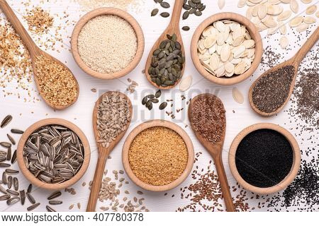 Healthy seeds - sesame, flax seed, sunflower seeds, pumpkin seed, chia and black seed in wooden spoons and bowls on a white background. Top view