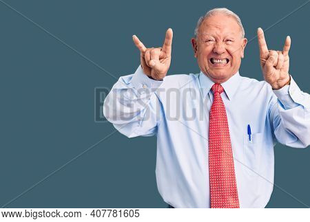 Senior handsome grey-haired man wearing elegant tie and shirt shouting with crazy expression doing rock symbol with hands up. music star. heavy concept.