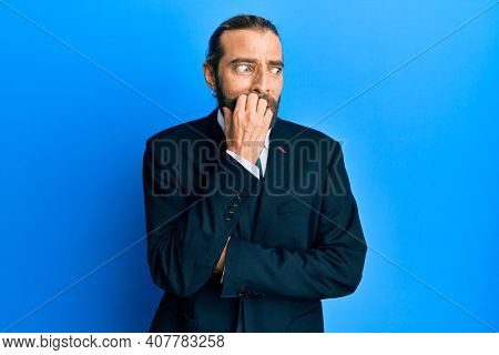Attractive man with long hair and beard wearing business suit and tie looking stressed and nervous with hands on mouth biting nails. anxiety problem.