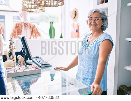 Middle age shop assistance woman working at the counter of retail shop smiling happy