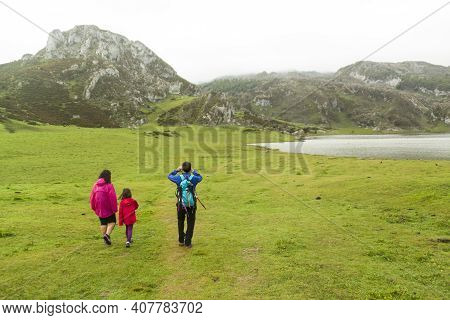 Lakes Of Covadonga With Fog In Spring. Tourists Hiking On Lake Enol. Asturias, Spain