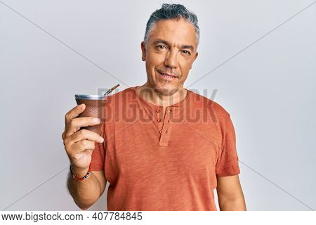 Handsome middle age mature man drinking mate infusion looking positive and happy standing and smiling with a confident smile showing teeth