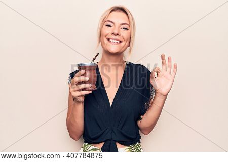 Young beautiful blonde woman drinking cup of mate infusion beverage over white background doing ok sign with fingers, smiling friendly gesturing excellent symbol